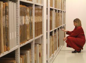 Archivarin vor dem Regal mit Grrundbüchern