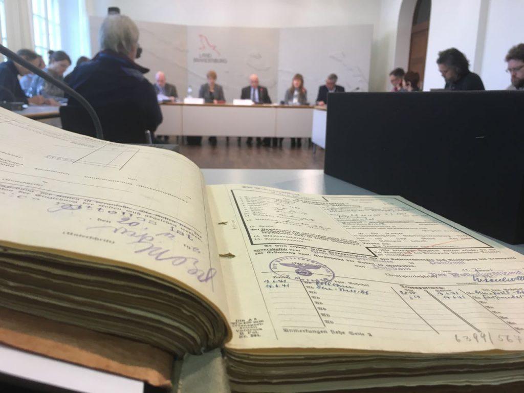 Bild zeigt Akte mit NS-Formularen, im Hintergrund die Teilnehmer der Pressekonferenz