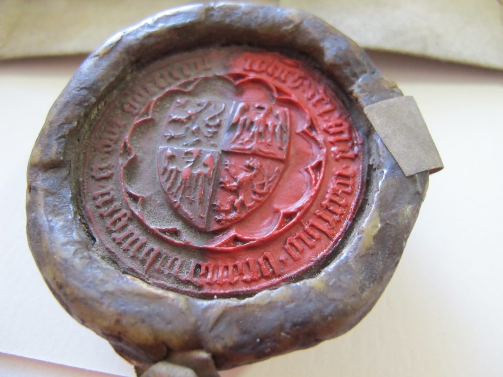 Bild zeigt ein rotes Wachssiegel, das zur Hälfte restauriert ist