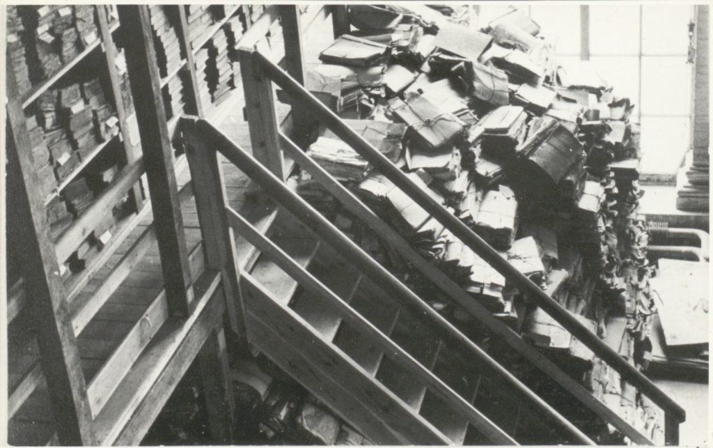 Ein Schwarz-Weiß-Foto zeigt Aktenberge an einer Treppe am alten Standort der Orangerie um 1950
