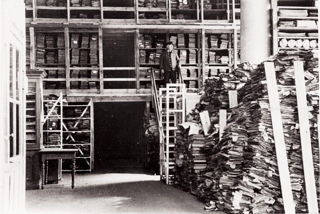 Ein Schwarz-Weiß-Foto zeigt, wie ein Mann von einem Podest auf riesige Aktenberge schaut.