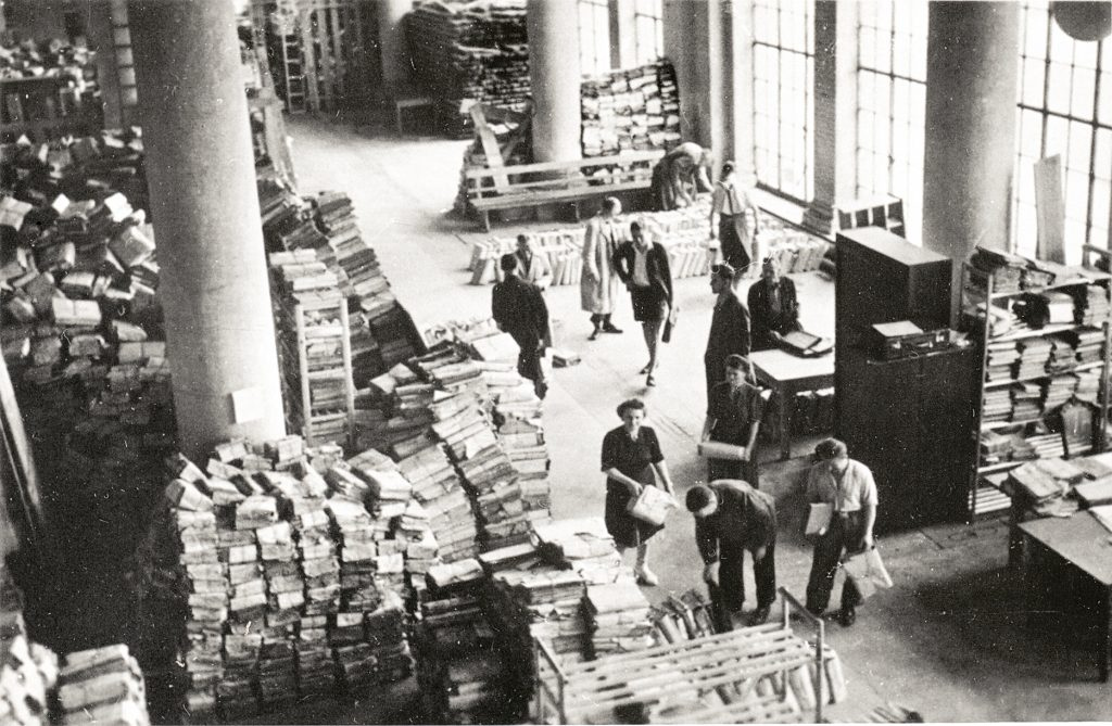 Ein Schwarz-Weiß-Foto zeigt Mitarbeitende in einer großen Halle, die Aktenberge sortieren