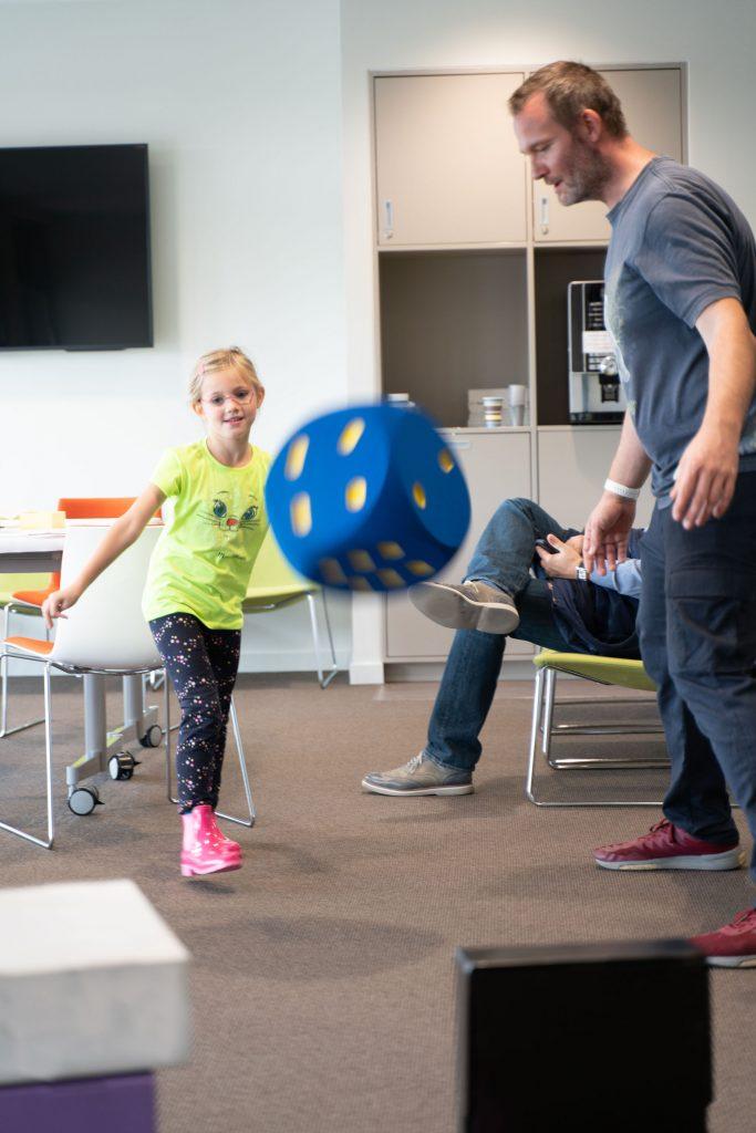 Ein Mann spielt mit einem Kind das Archiv-Make'N'Break im Foyer