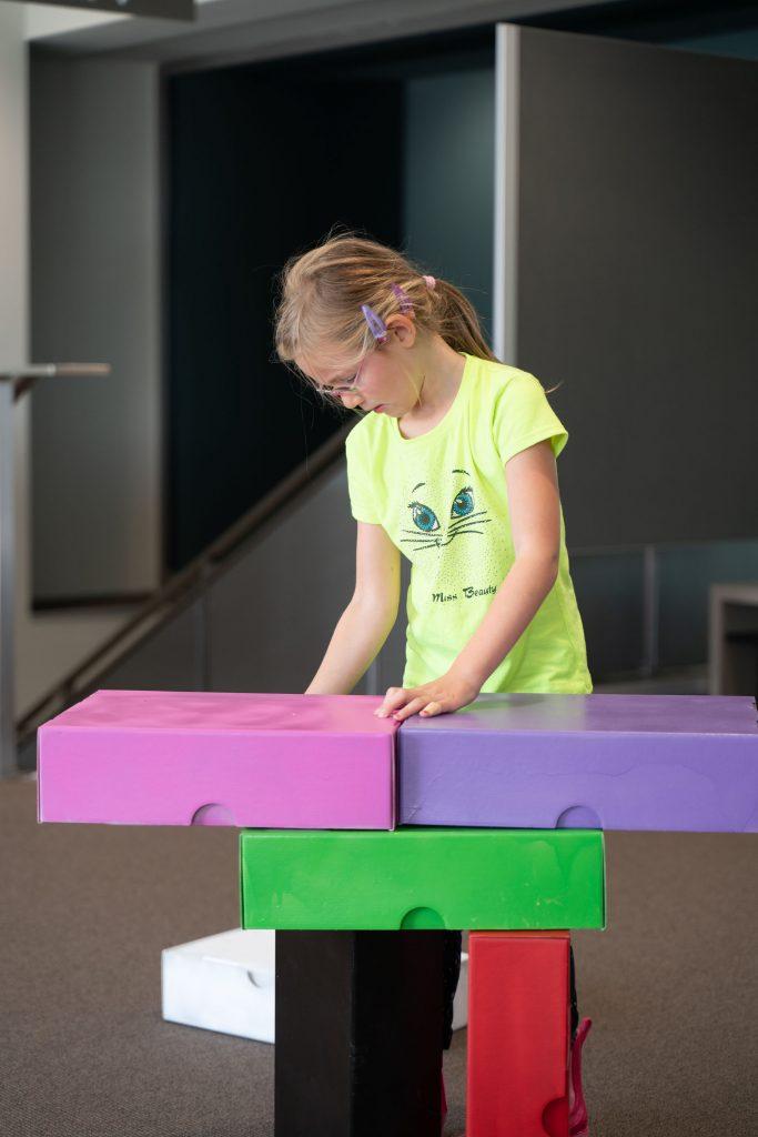 Ein Kind baut einen Turm aus bunten Archivkartons