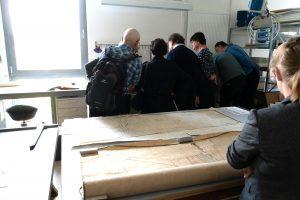 Besucher bekommen etwas in der Restaurierungswerkstatt durch einen Mitarbeitenden zu sehen