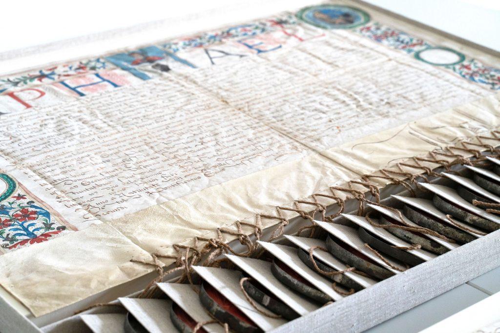 Eine Urkunde befindet sich auf einem Tisch vor der Digitalisierung