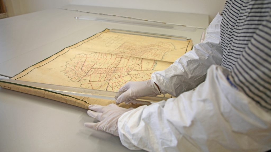 Papier-Restauratorin mit Handschuhen beim Planlegen einer Karte mittels Auflegung von Gewichten