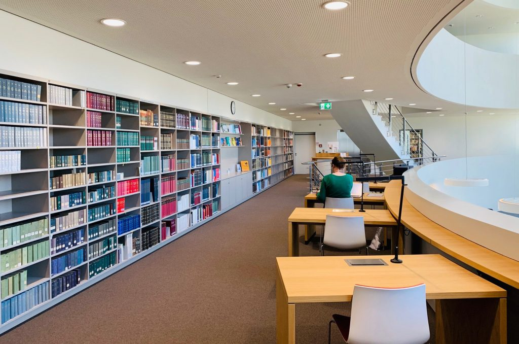 Eine Nutzerin in der Bibliothek vor den Regalen des Freihandbestands