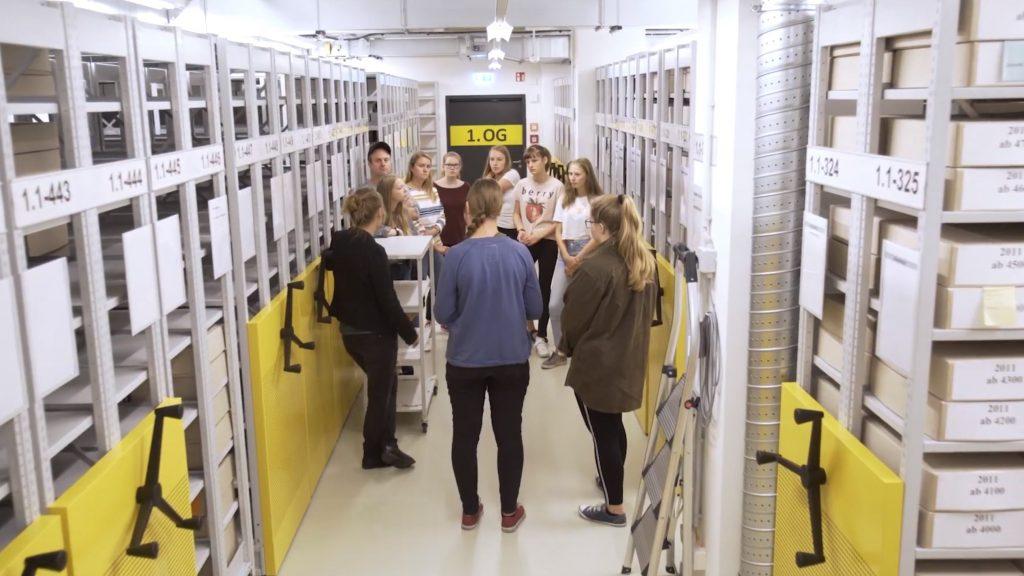 Schülerinnen des Hannah-Arendt-Gymnasiums stehen im Gang eines Magazins des BLHA