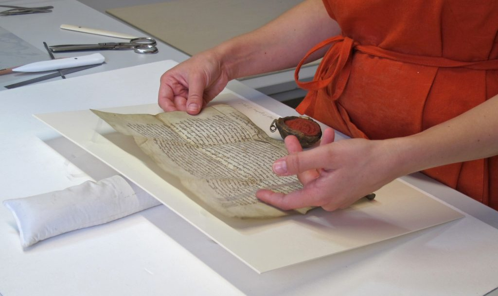 Eine restauratorin montiert eine Urkunde mit Siegel auf Karton